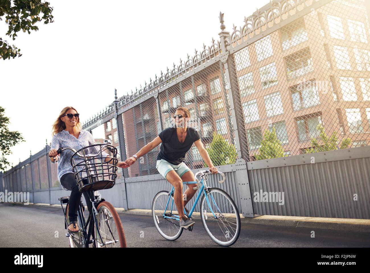 Romantisches Paar Hände halten, wie sie Rad fahren Reiten ihre Fahrräder in einer städtischen Straße Stockbild