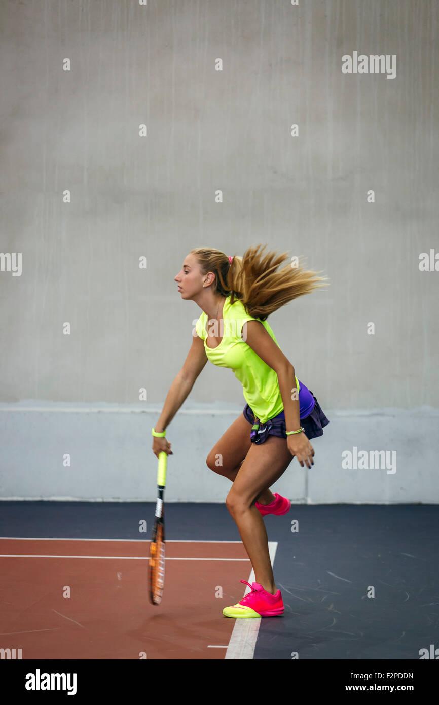 Junge Frau mit dem Tennisspielen in eine Tennishalle Stockbild