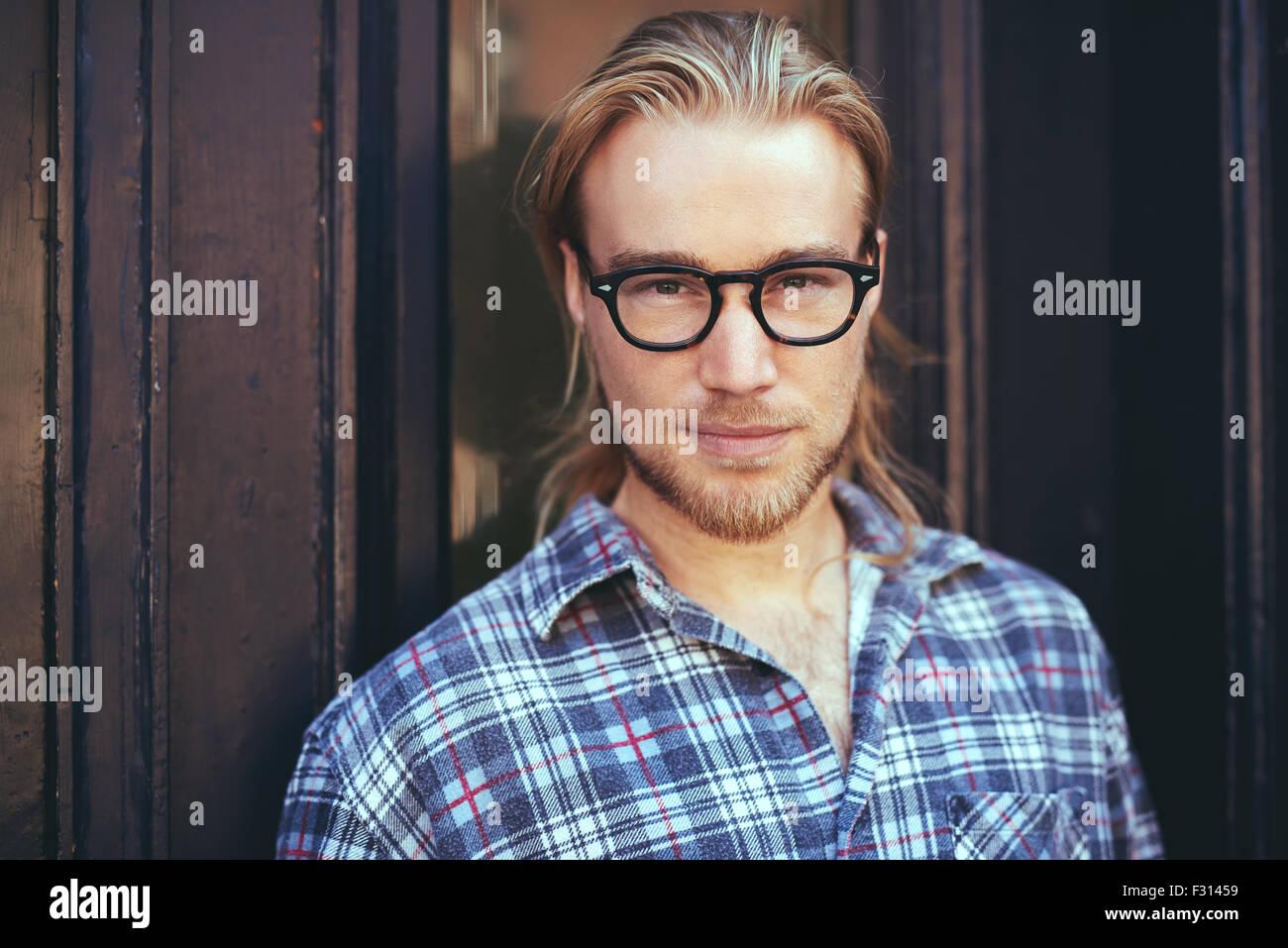 Closeup Portrait von blonder Mann mit langen Haaren und Brille. nachdenklicher Mann Stockbild