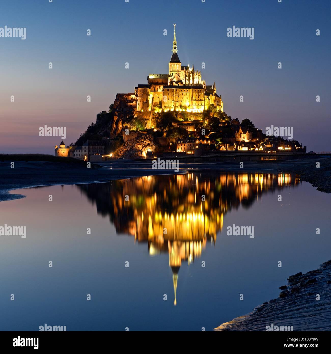 Ein Farbbild von Reflexionen des Mont Saint Michel leuchtet in der Dämmerung in einen Pool am Strand von Mont Stockbild