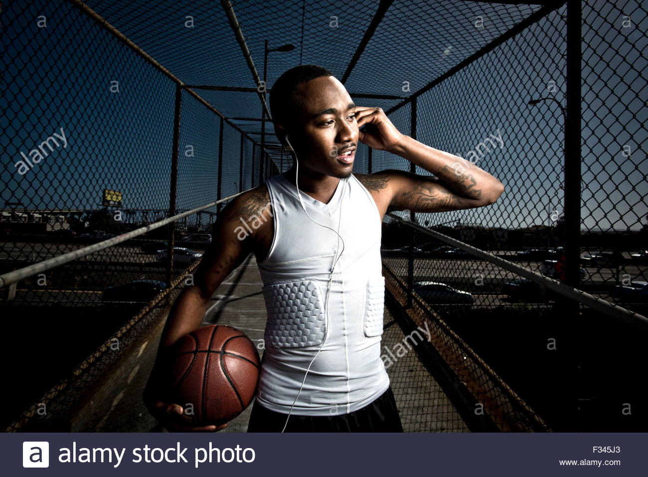 Ein Basketball-Spieler geht auf eine Fußgängerbrücke. Stockbild