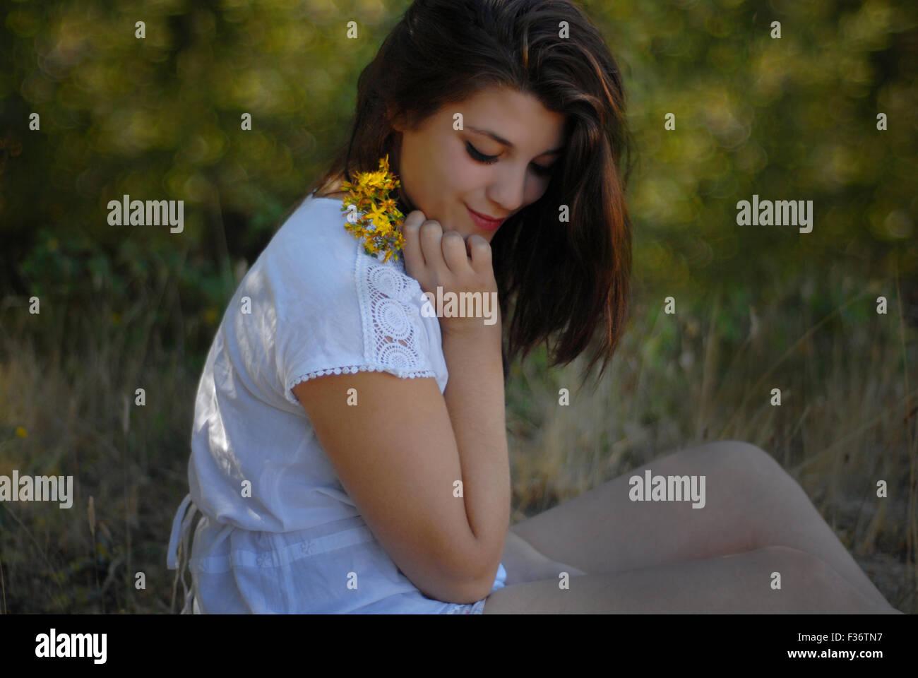 Beauty Mädchen blickte mit gelben Blüten in ihren Händen in einem weißen Kleid Stockbild