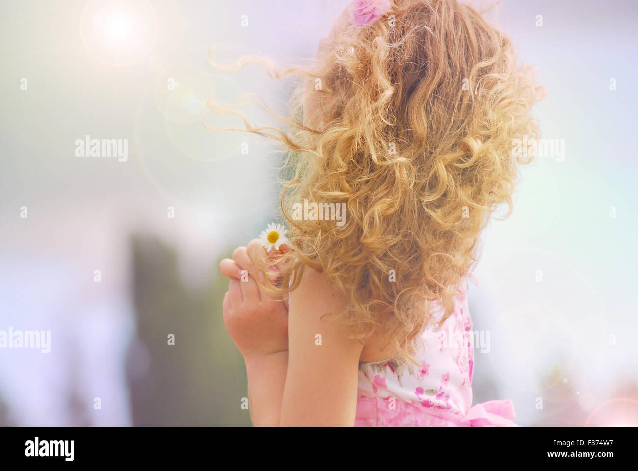 niedliche kleine Mädchen mit Blume in den Händen suchen die Sonne und der Himmel Stockbild
