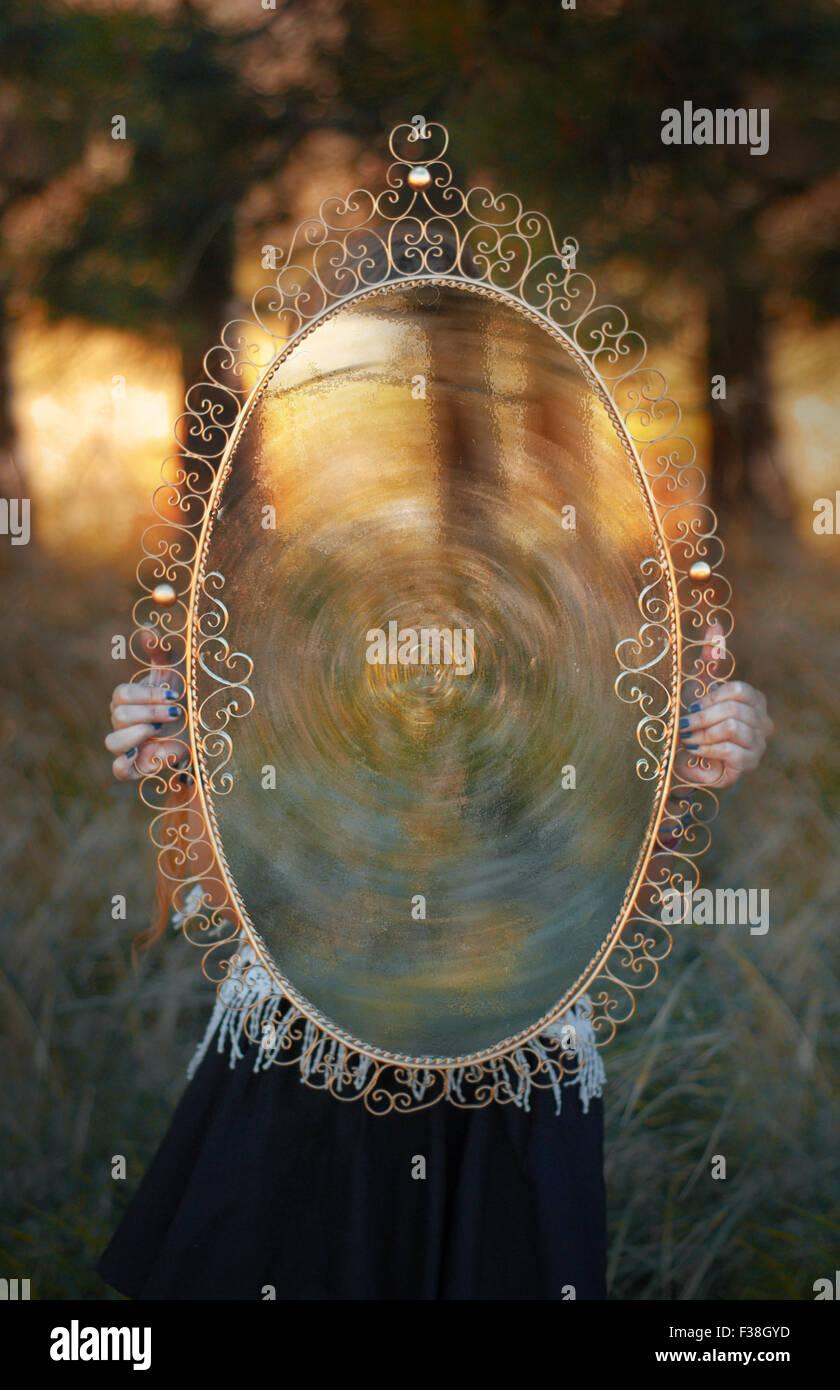 Mädchen mit einem großen antiken Spiegel im Wald Portal in eine andere dimension Stockbild