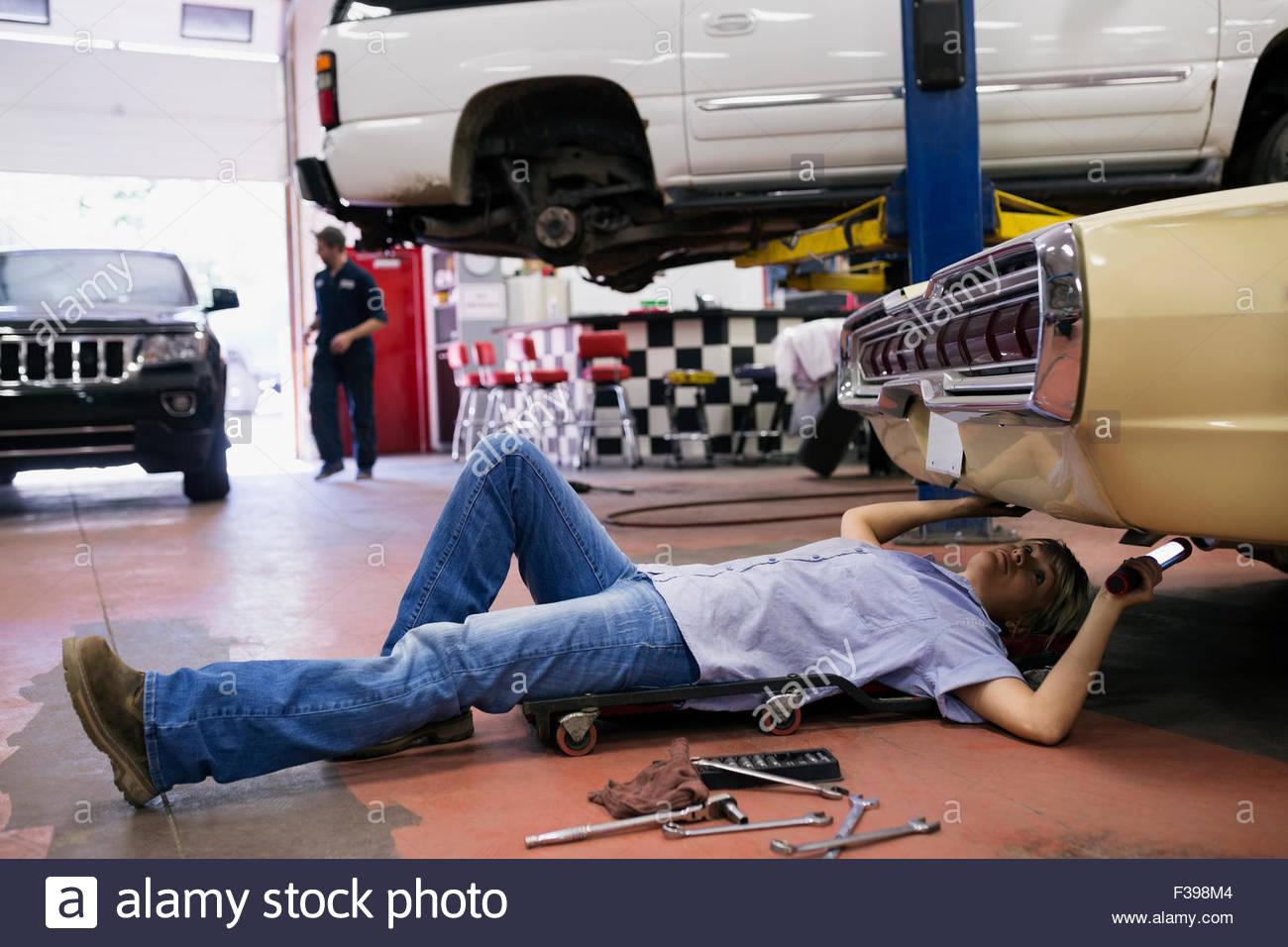Weibliche Mechaniker unter Auto in Auto-Werkstatt Stockbild
