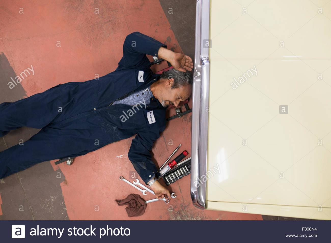 Draufsicht Mechaniker für Werkzeug unter dem Auto zu erreichen Stockbild