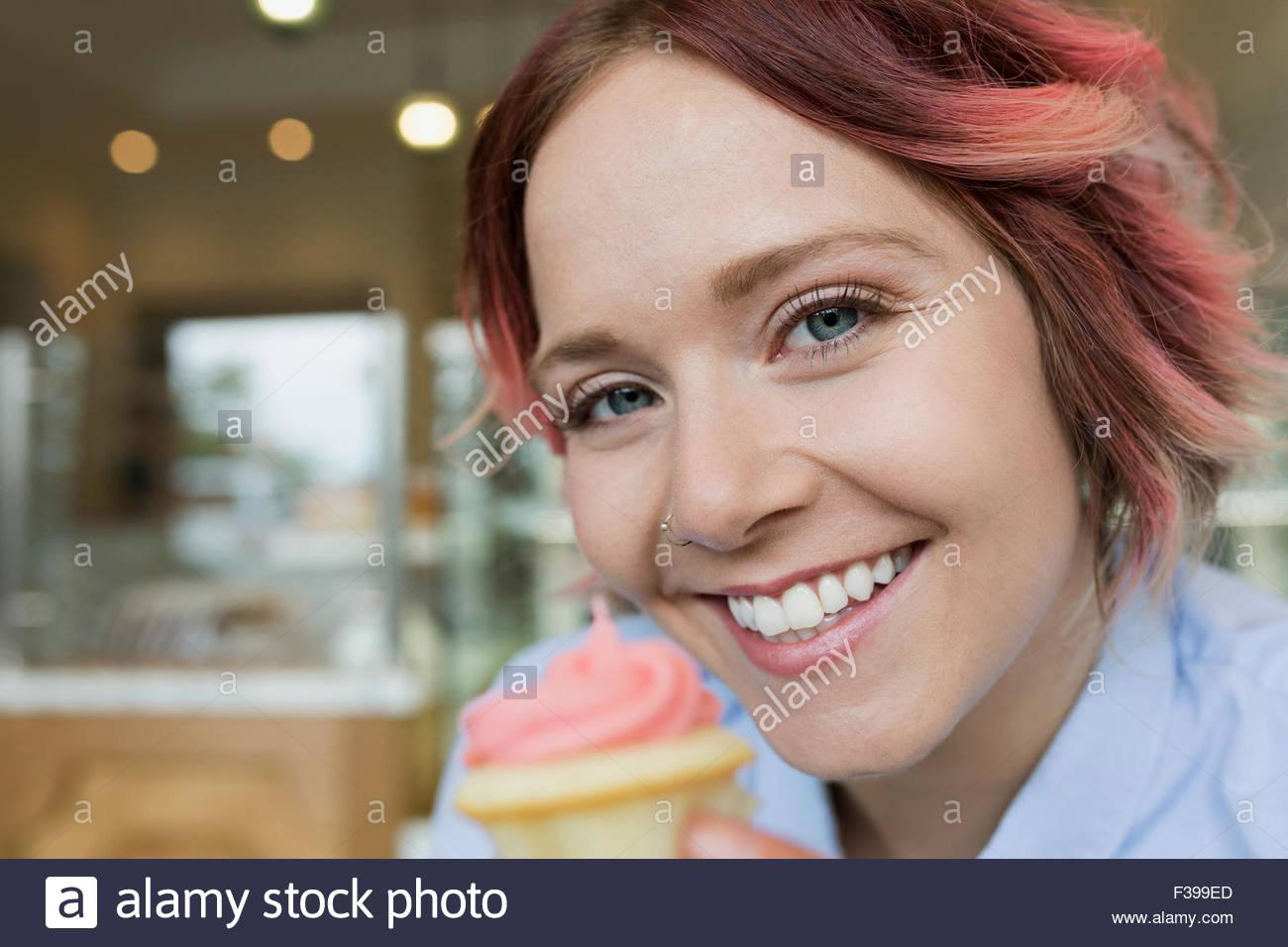 Nahaufnahme Hochformat lächelnde Frau mit rosa cupcake Stockbild