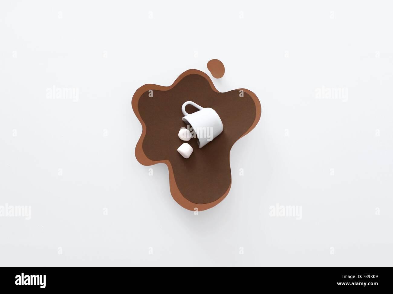 Konzeptionelle Becher umgeworfen, liegend in einem Pool von Papier gemacht, heißen Schokolade mit marshmallows Stockbild