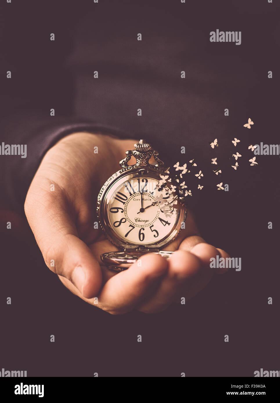 Mann, der eine Uhr mit der Zeit aus dem Zifferblatt wie Schmetterlinge fliegen in seiner Hand hält Stockbild