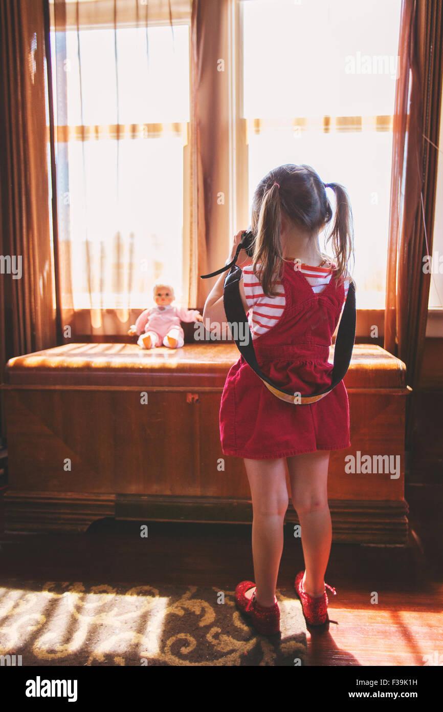 Mädchen, die ein Foto von ihrem Spielzeugpuppe Stockbild