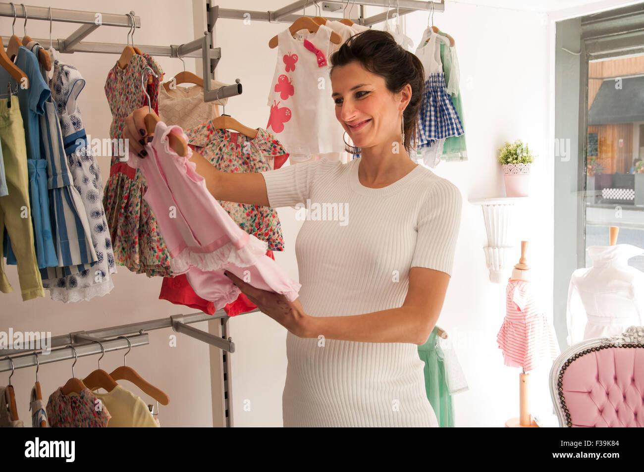 Porträt einer lächelnden schwangeren Frau in einem Geschäft Blick auf Baby-Kleidung Stockbild
