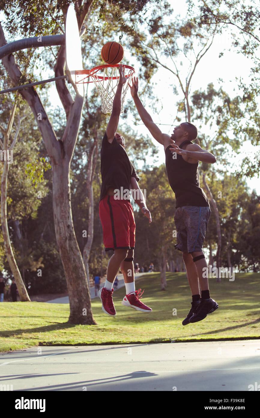 Zwei junge Männer schießen Basketballkörbe im Park bei Sonnenuntergang Stockbild