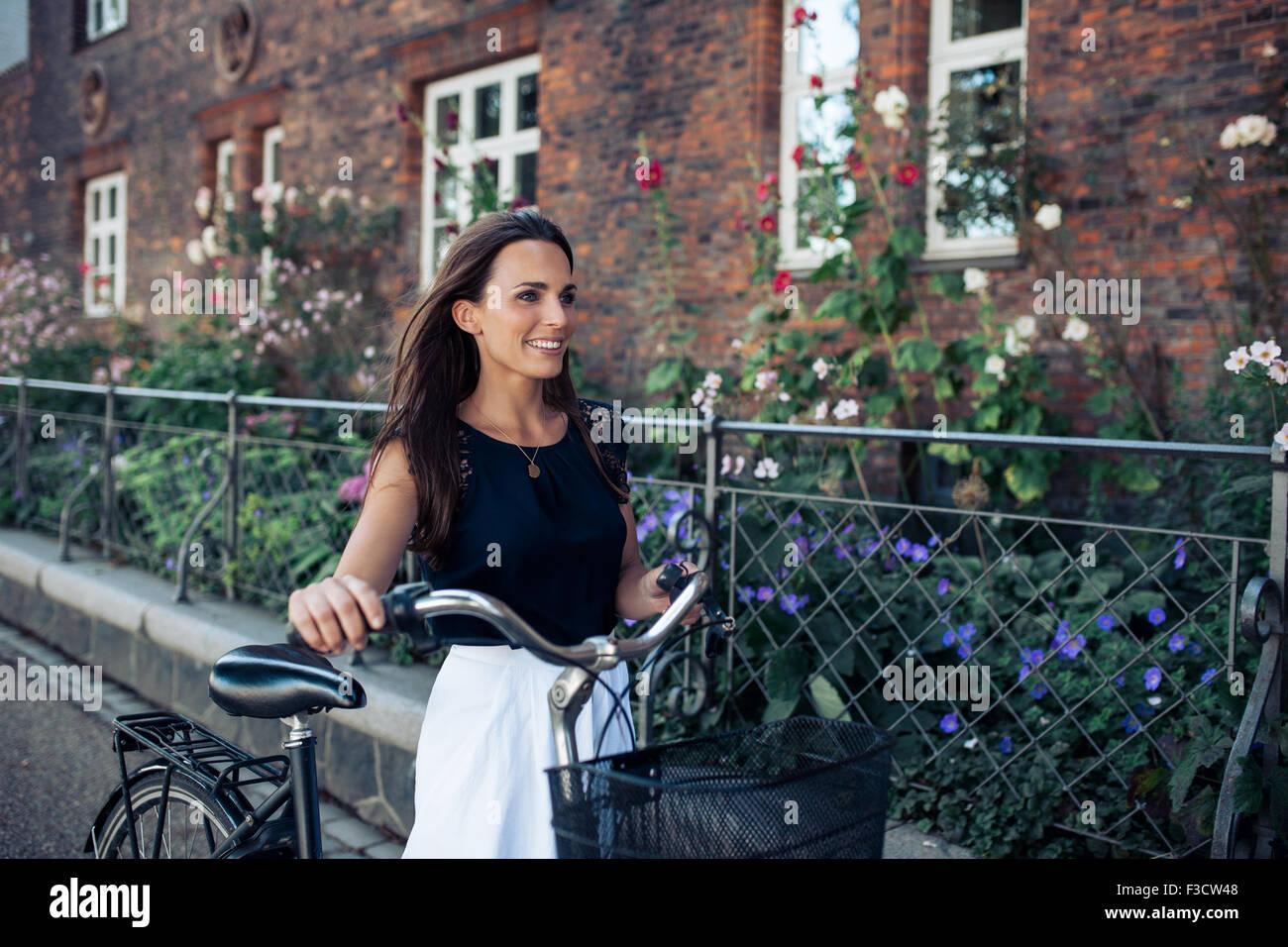 Porträt der schönen jungen Frau, die entlang der Straße mit dem Fahrrad. Frau mit Fahrrad, zu Fuß Stockbild