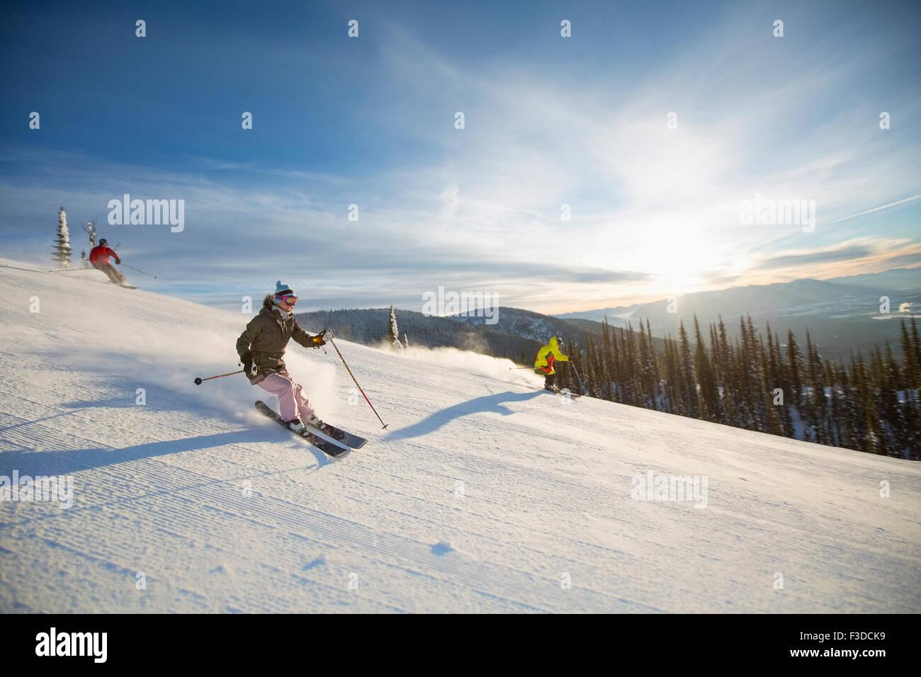 Drei Menschen auf der Skipiste im Sonnenlicht Stockbild