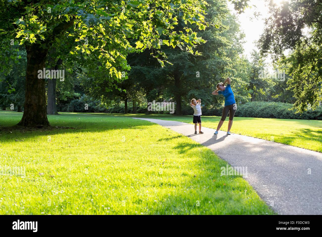Mutter und Sohn (12-13) Gymnastik im park Stockbild