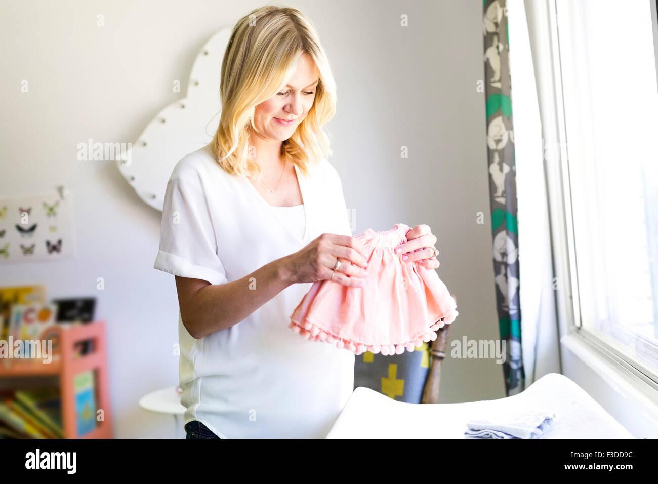 Schwangere Frau halten Baby Kleidung Stockbild