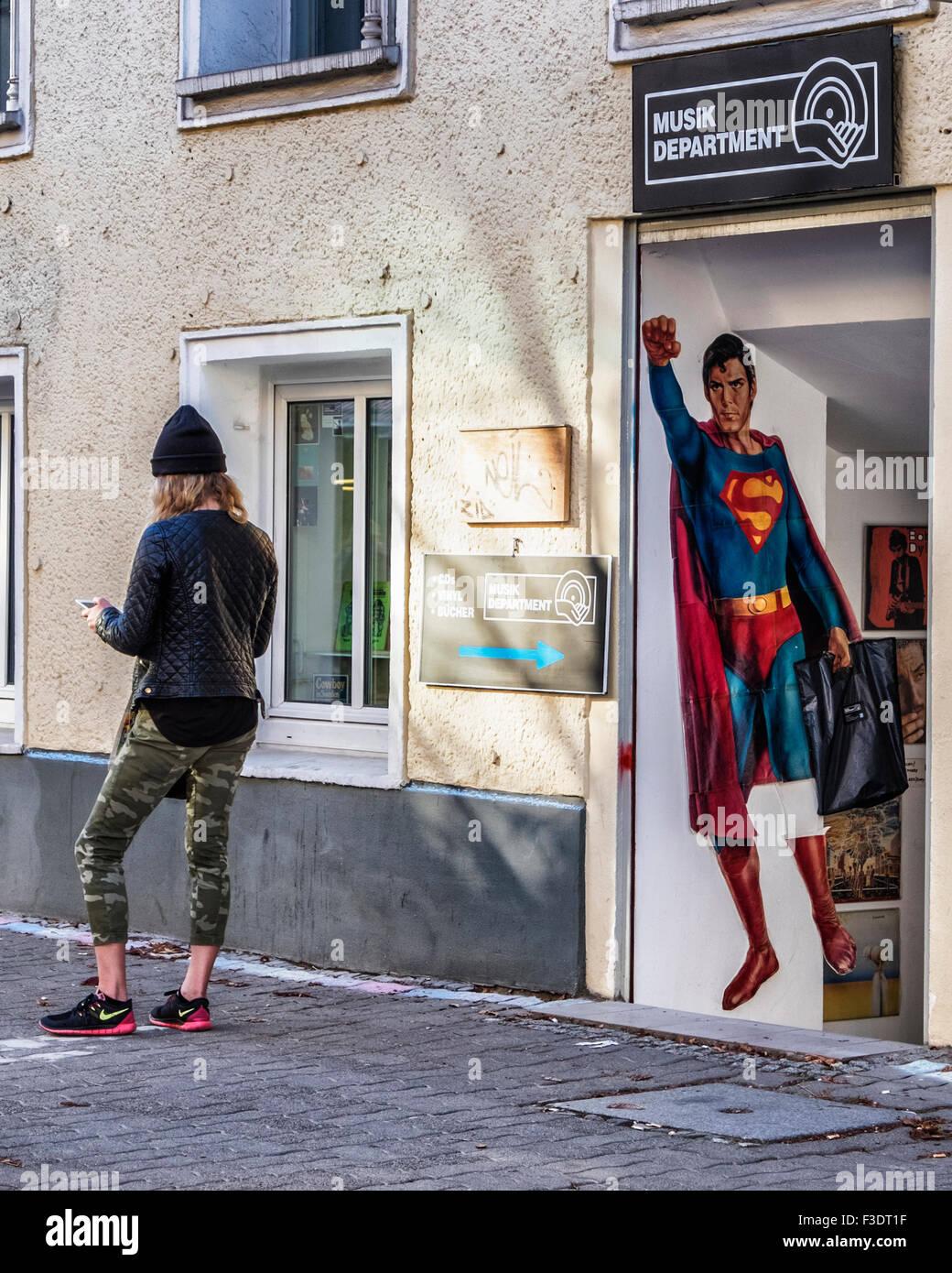 Musik-Kaufhaus Verkauf von CDs und Vinyl mit Superman Anzeige und Frau mit Tablettcomputer außerhalb Store, Stockbild