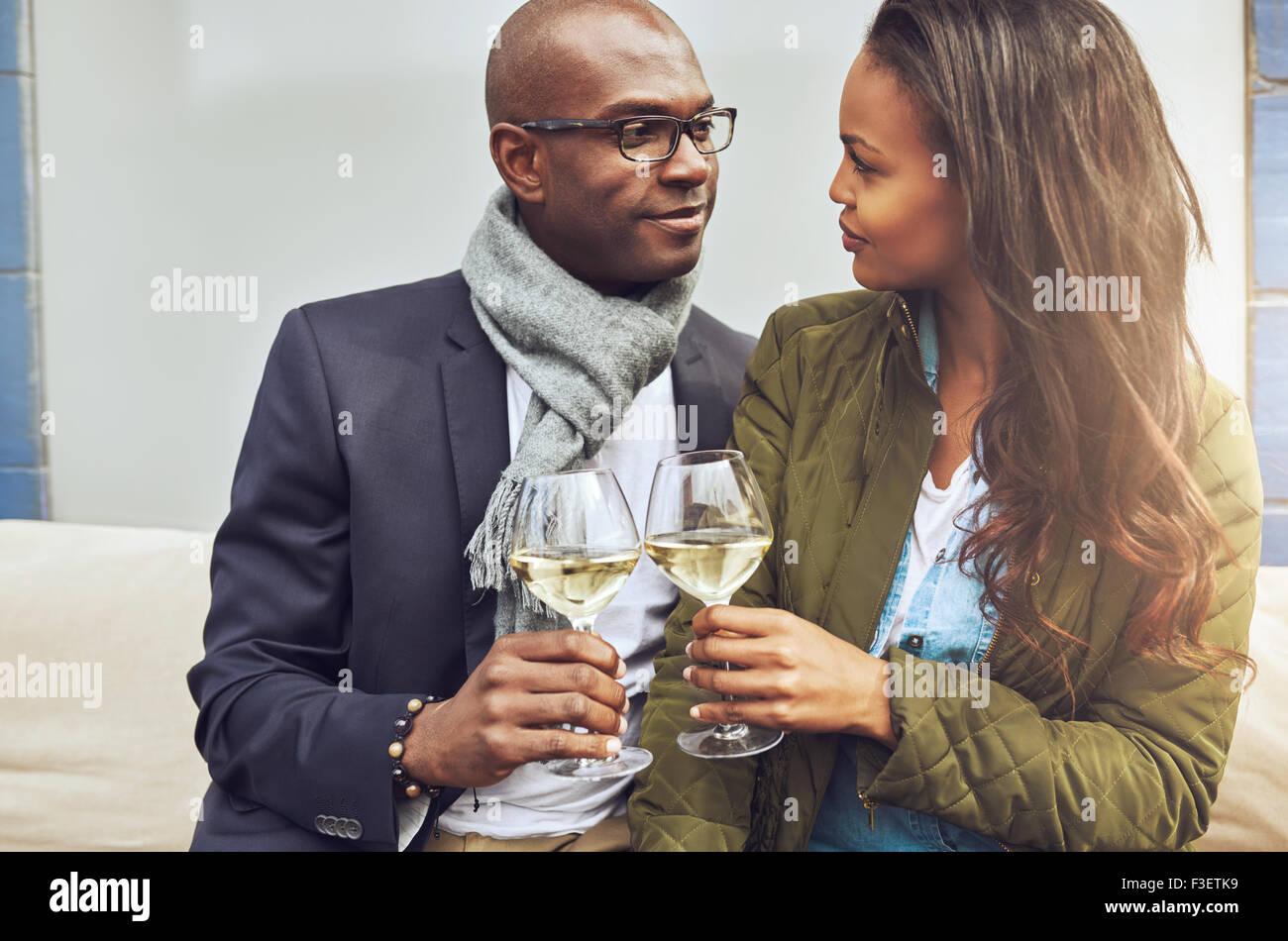 Liebevolle afrikanische amerikanische Paar in eine enge Umarmung einander Toasten mit Weißwein, wie Sie tief Stockbild