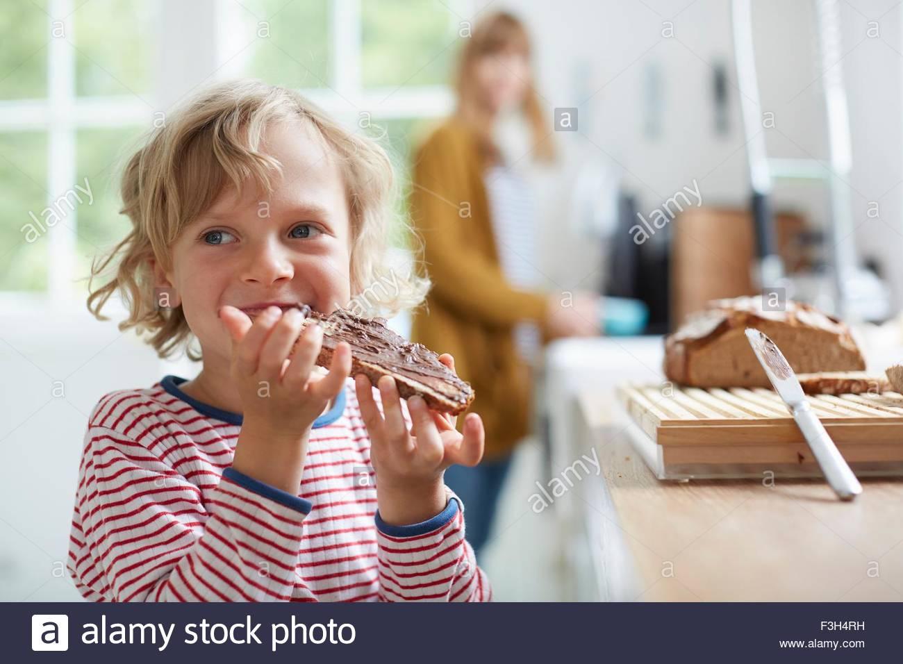 Kleiner Junge essen Brot mit Schokolade zu verbreiten, Mutter im Hintergrund Stockbild