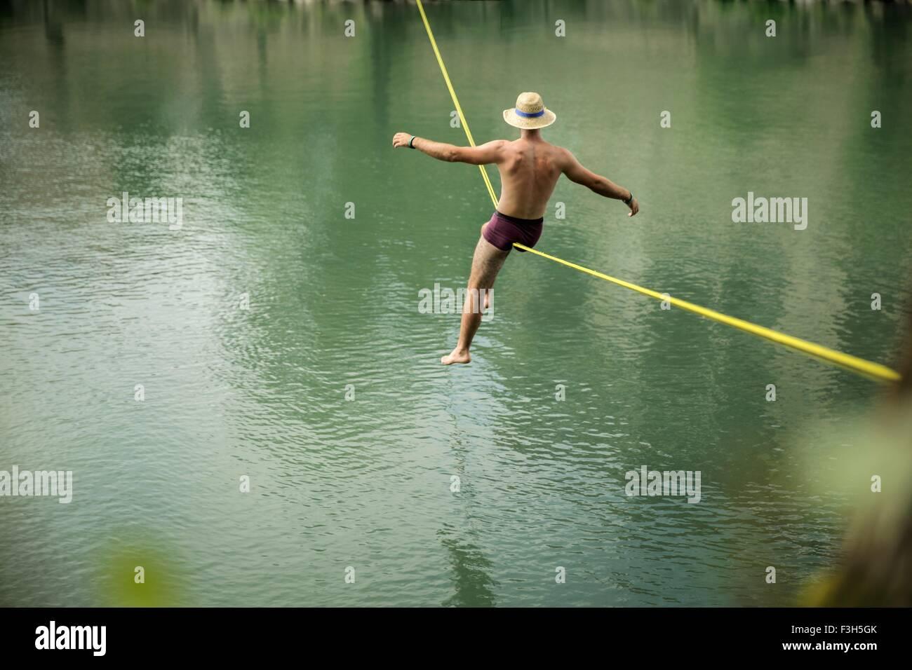 Reifer Mann balancieren auf Seil über See, Rückansicht Stockbild