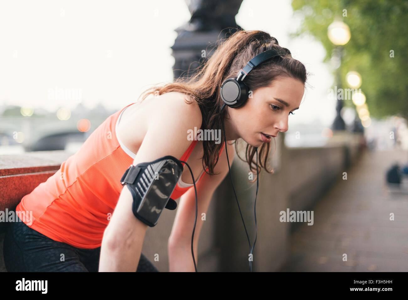 Weibliche Läufer tragen von Kopfhörern eine Pause am Ufer erschöpft Stockbild