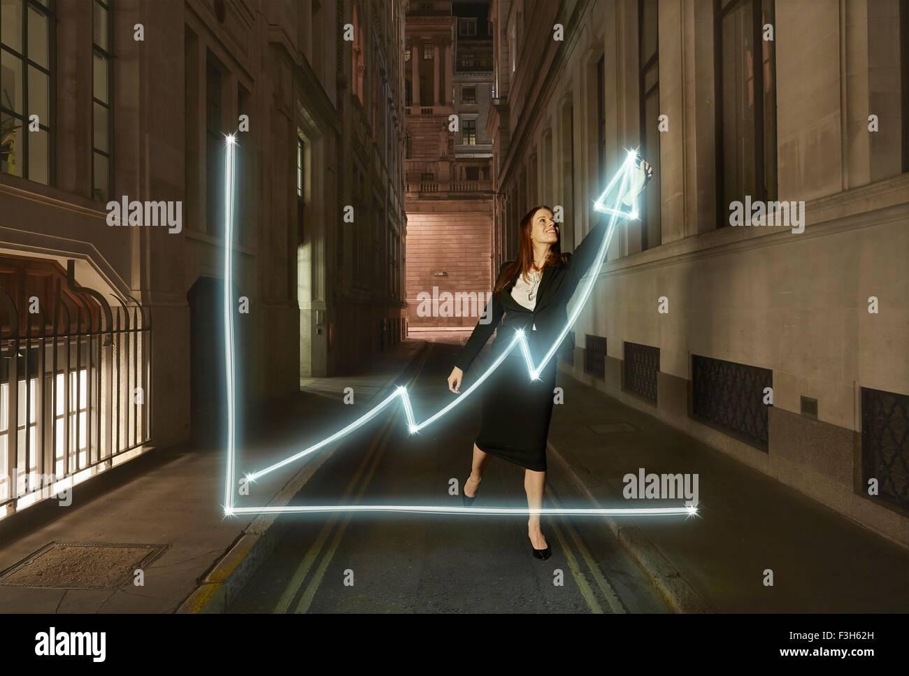 Geschäftsfrau Lichtmalerei glühende Diagramm mit nach oben Pfeil-Symbol auf der Stadtstraße in der Stockbild