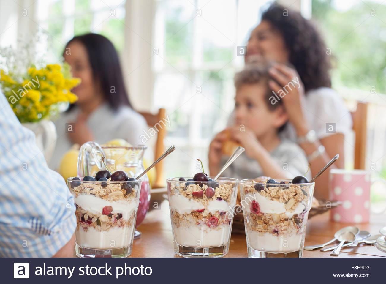 Familie genießen Mahlzeit zusammen, Fokus auf Desserts im Vordergrund Stockbild