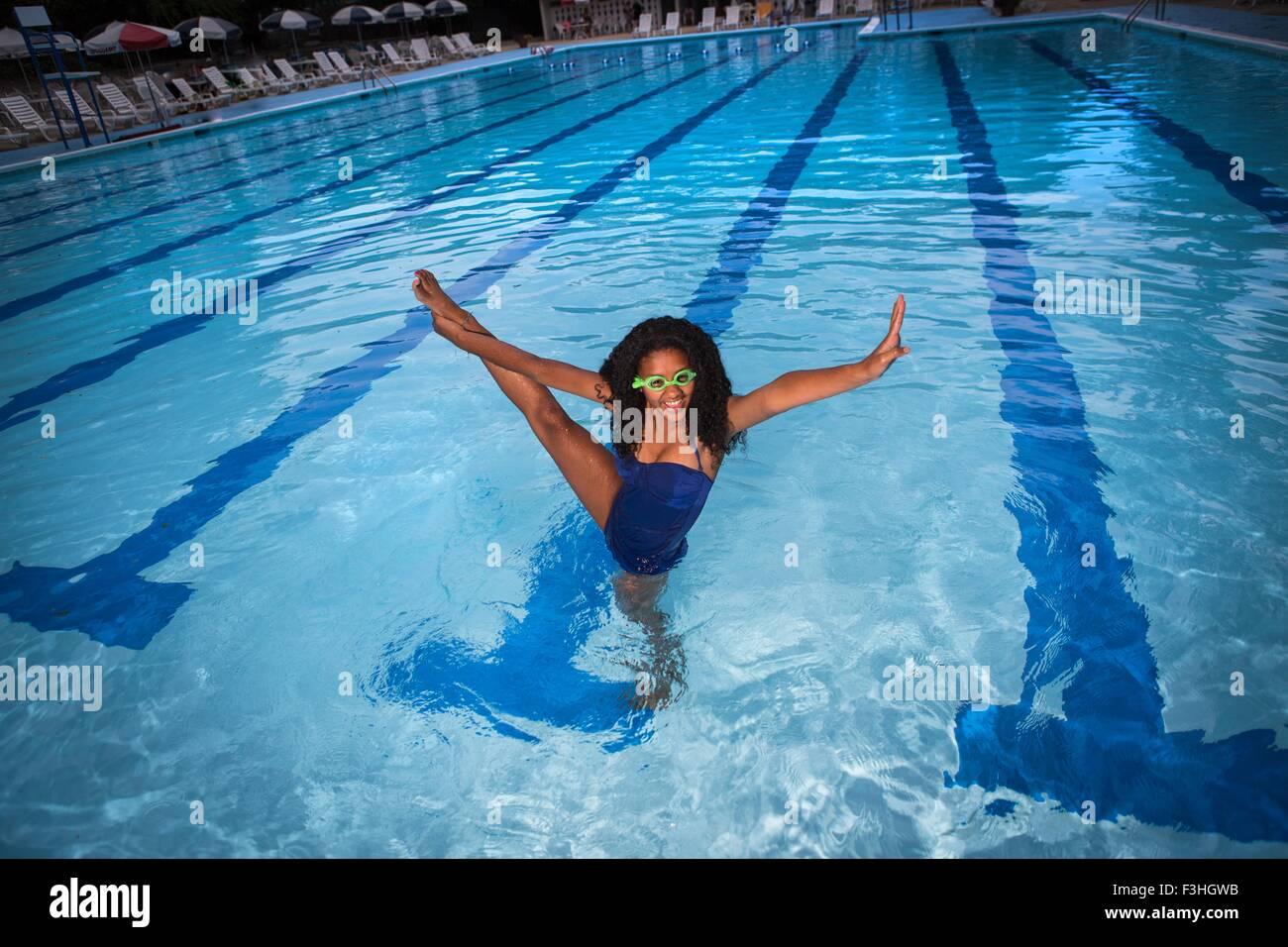 Porträt von Mädchen stehen auf einem Bein im Schwimmbad tragen von Schutzbrillen, Bein angehoben, Blick Stockbild