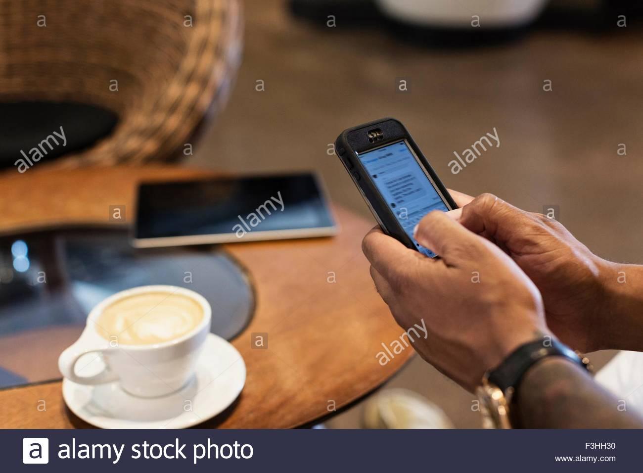Junger Mann in Coffee-Shop mit Smartphone, Fokus auf Händen Stockbild