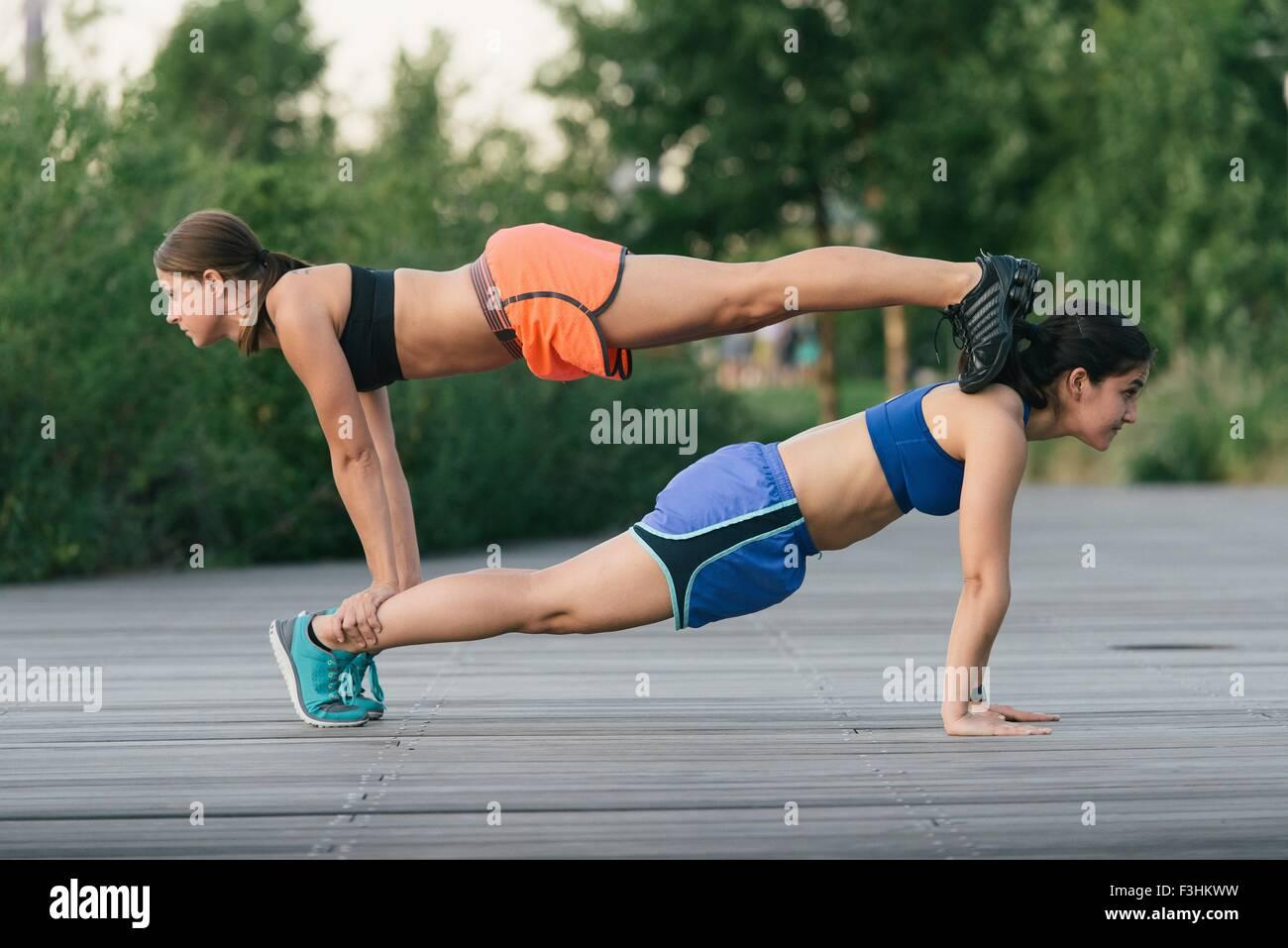 Zwei Freunde trainieren zusammen und helfen einander balancieren auf Push zurück zu tun USV Stockbild