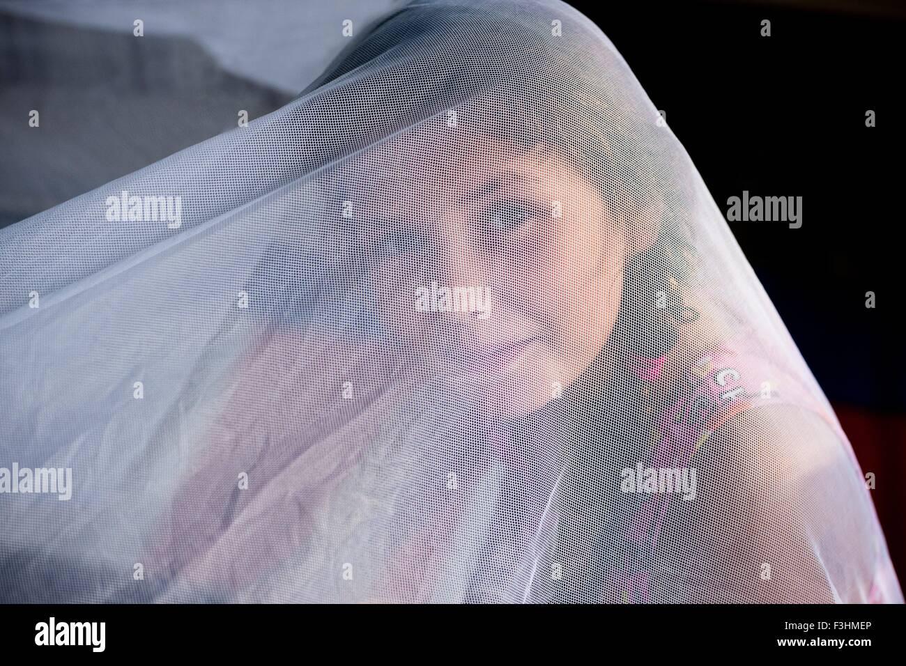 Mädchen unter weißen netting-Blick auf die Kamera zu Lächeln Stockbild