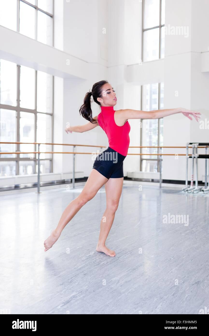 Junge Frau im Tanzstudio tanzen Arme öffnen wegschauen Stockbild