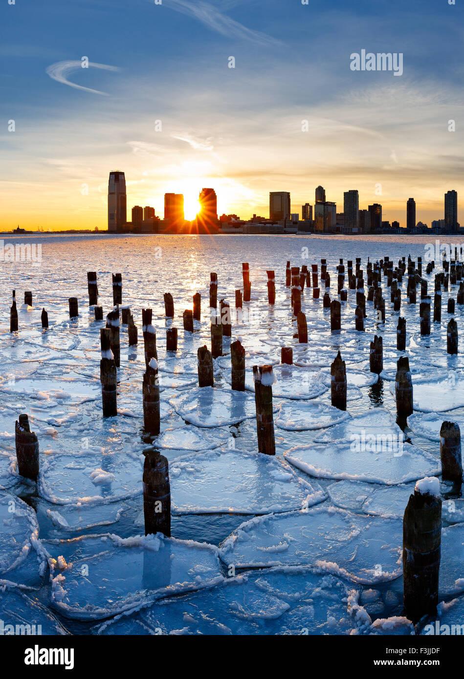 Holz Pfähle aus New York alten Pier bei Sonnenuntergang mit Jersey City Gebäude durch das Eis am Hudson Stockbild