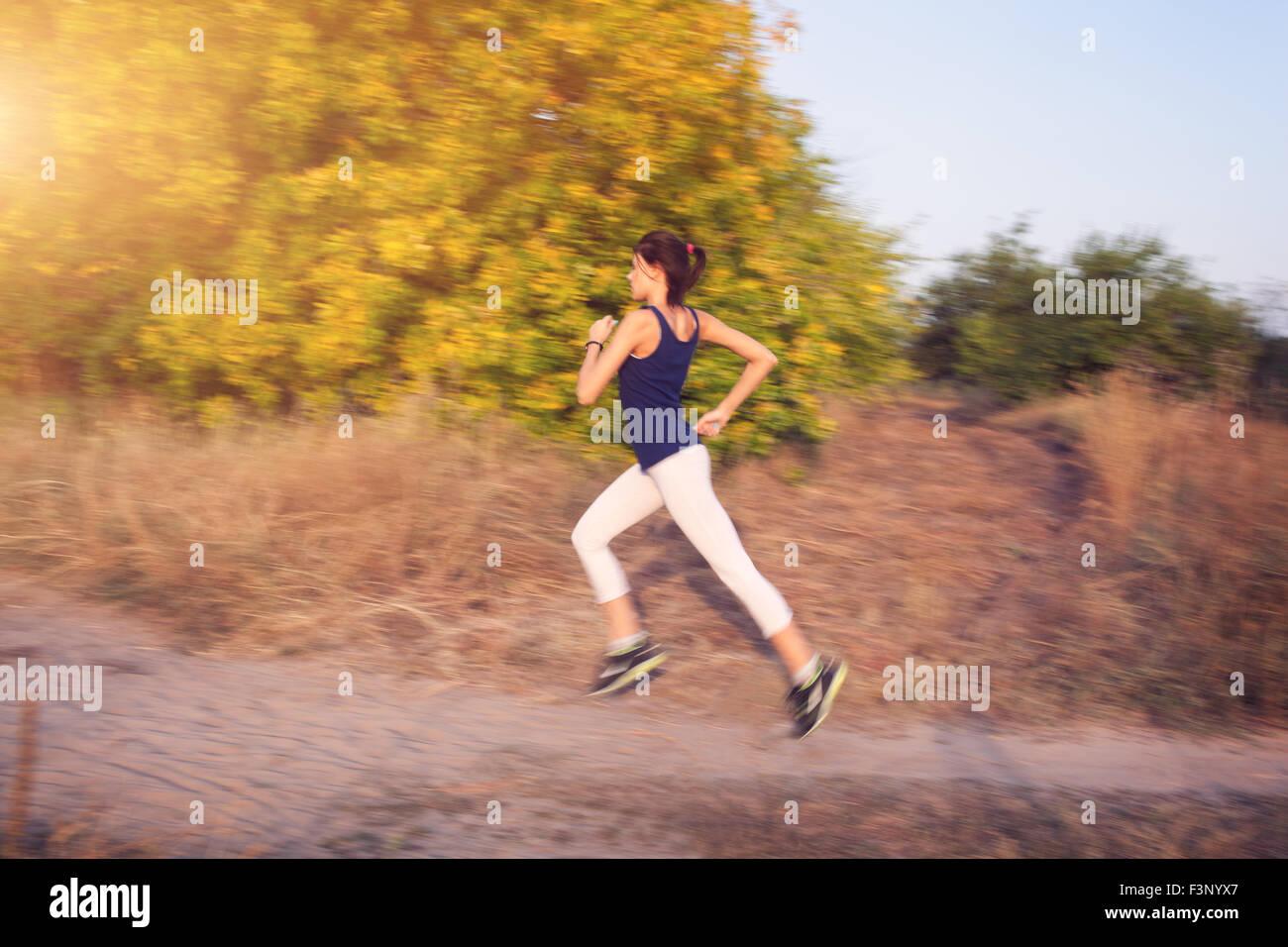 Junge Frau auf einer Landstraße bei Sonnenuntergang im herbstlichen Wald ausgeführt. Lifestyle-Sport-Hintergrund Stockbild