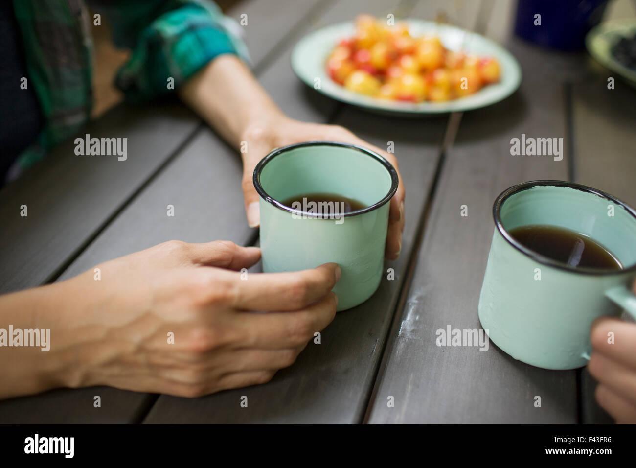 Zwei Personen an einem Tisch sitzen, Kaffee trinken, von oben gesehen. Stockbild