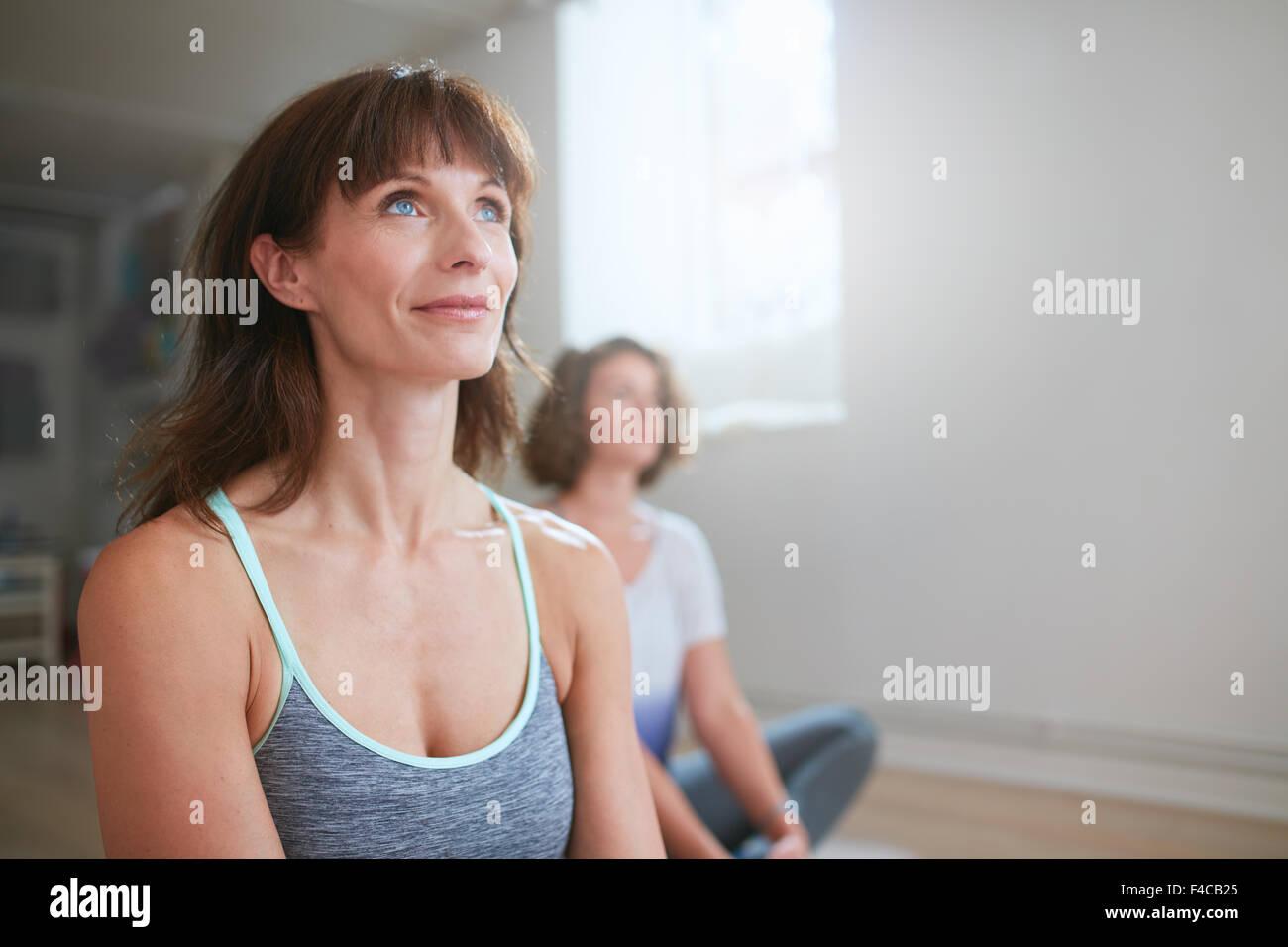 Porträt von Fitness-Frau sitzen auf Boden in Yoga-Klasse wegsehen. Yoga-Trainer während der Trainingseinheit Stockbild