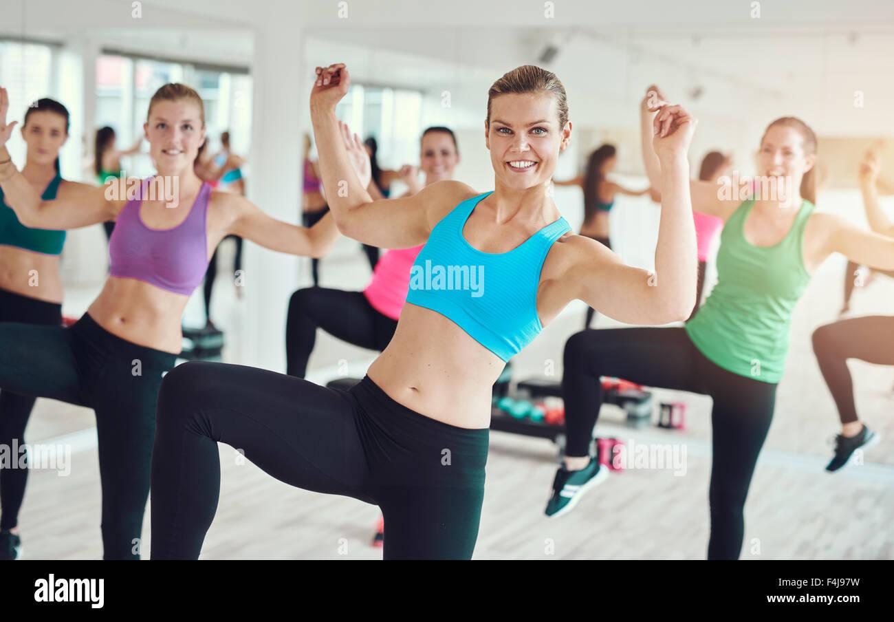 Gruppe von begeisterten jungen Frauen in bunten Kleidern üben Aerobic in der Turnhalle in einem Gesundheit Stockbild