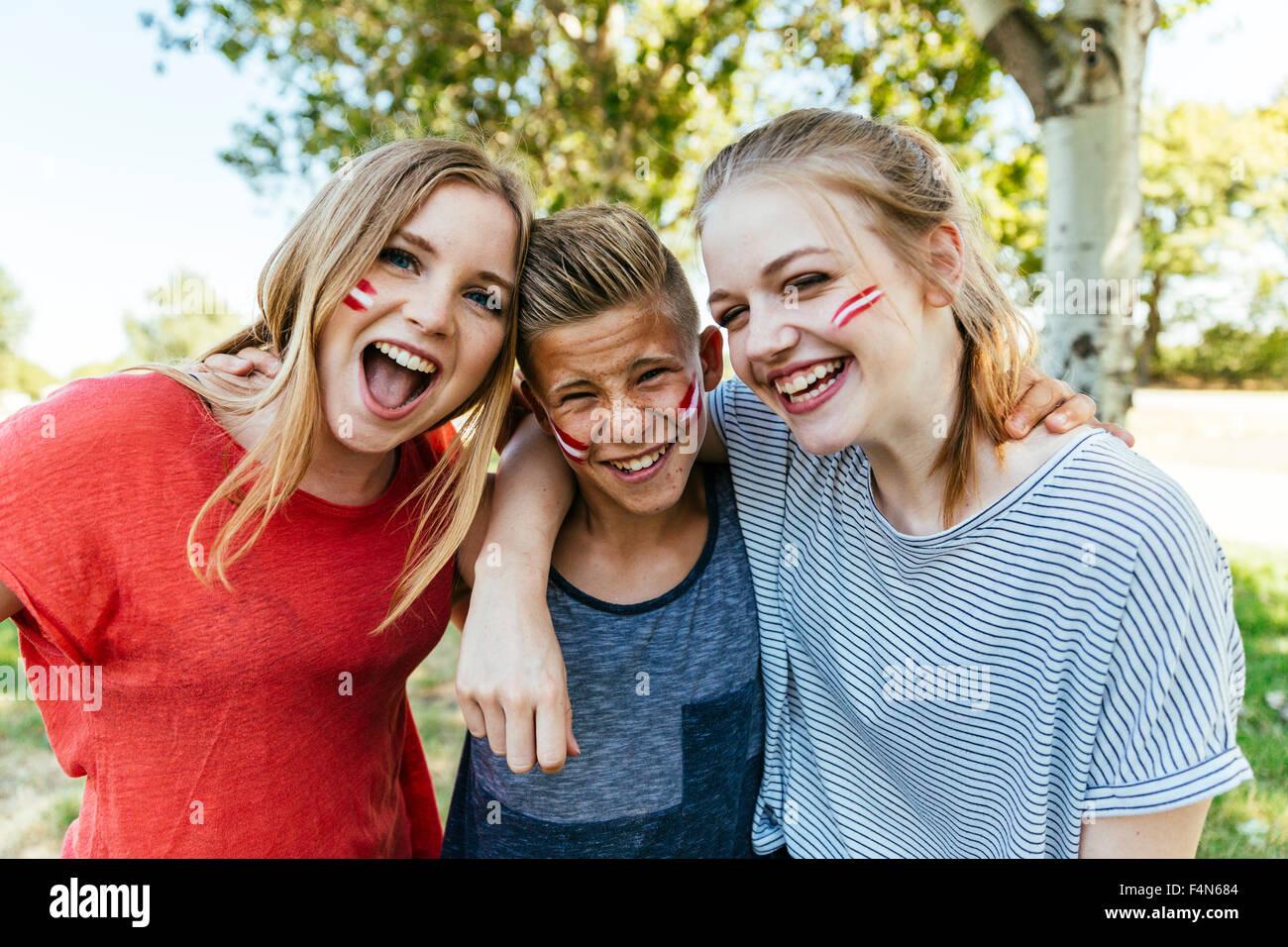 Österreich, drei Jugendliche mit nationalen Farben gemalt auf ihren Wangen gemeinsam feiern Stockbild