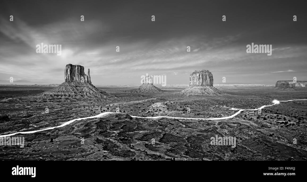 Schwarz / weiß Foto des Monument Valley mit Autolichter Routen in der Nacht, USA. Stockbild