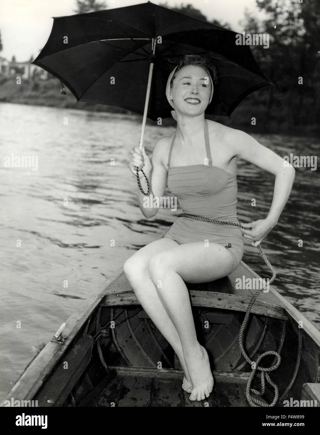 Britische Schauspielerin Joan Brown in Badeanzug und Sonnenschirm Stockbild