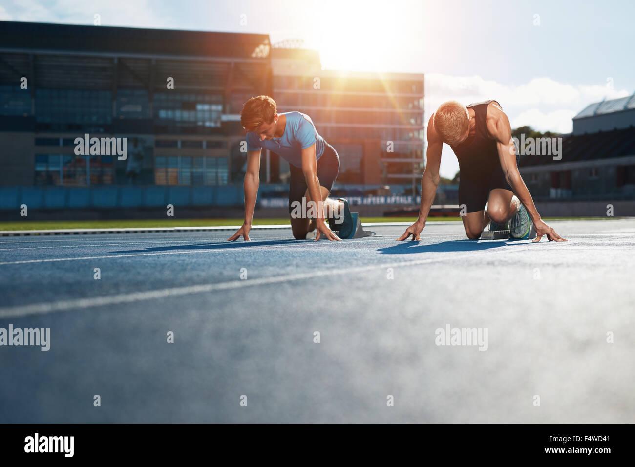 Junge Sportler in Start-Blöcke im Stadion Rennen vorbereiten. Sprinter in Startlöchern bereit für Stockbild