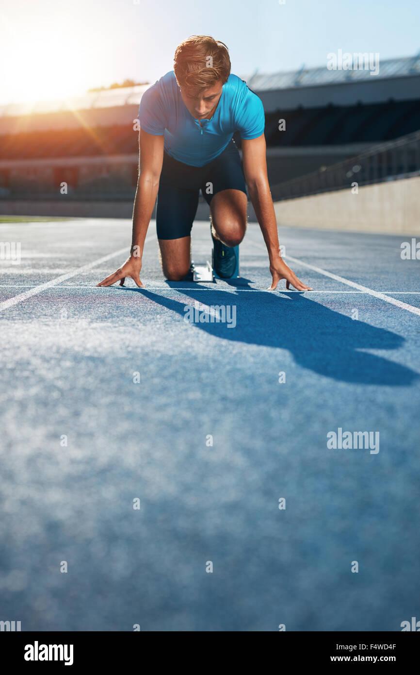 Professionellen männlichen Leichtathlet in soll-Position auf sprinten Blöcke von einer Leichtathletik Stockbild