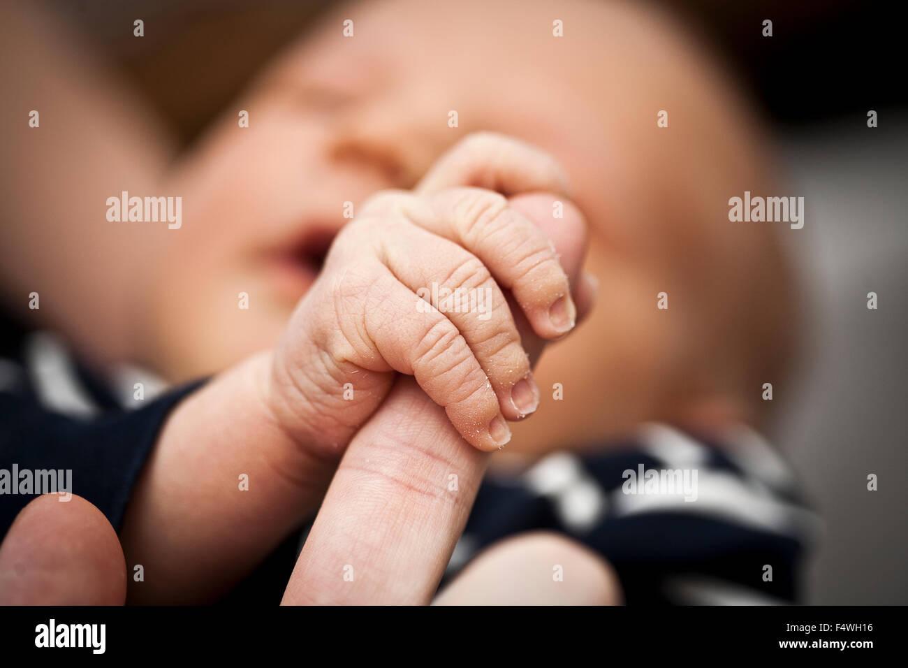 Junge (0-1 Monate) mit Vaters Finger Stockbild