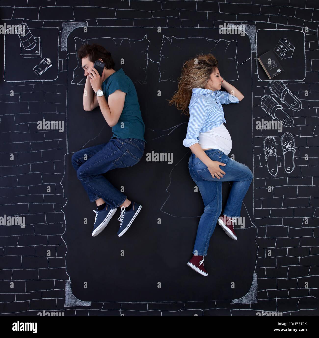 Junges Paar Aktivitäten im Bett zu tun. Der Mann ist am Telefon reden, während sie schläft. Stockbild
