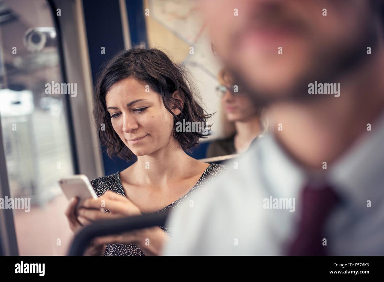 Eine Frau in einem Bus, blickte auf ihr Handy Stockbild