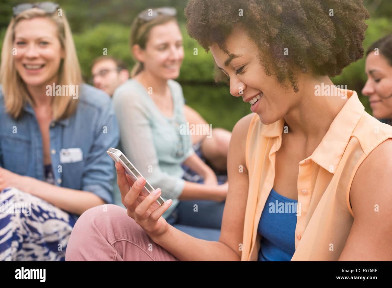 Eine Frau in einer Gruppe von Freunden, blickte auf ihr Handy Stockbild