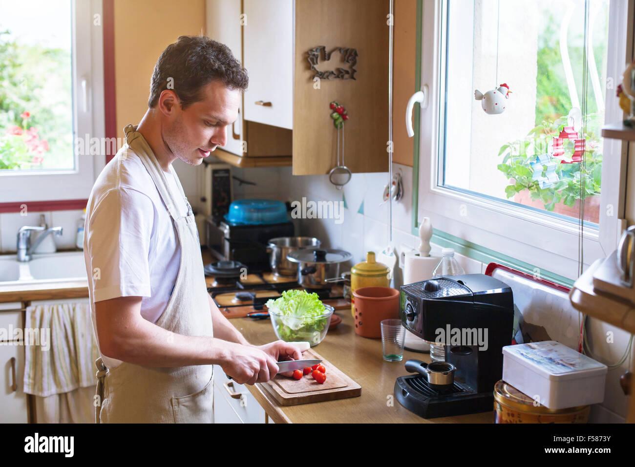 gesund kochen, junge männliche Beschneidung Tomaten in der Küche Stockbild