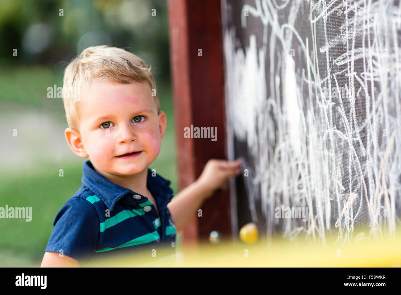 Kreative niedlichen Kleinkind zeichnen mit Kreide im freien Stockbild