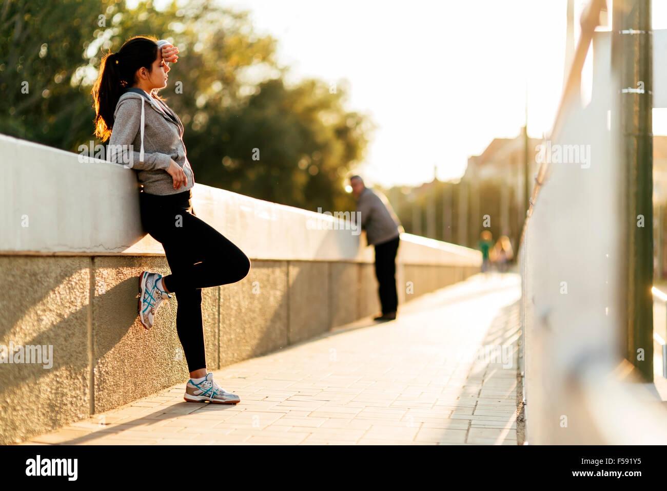 Schöne Frau ruht nach dem Joggen in Stadt Stockbild