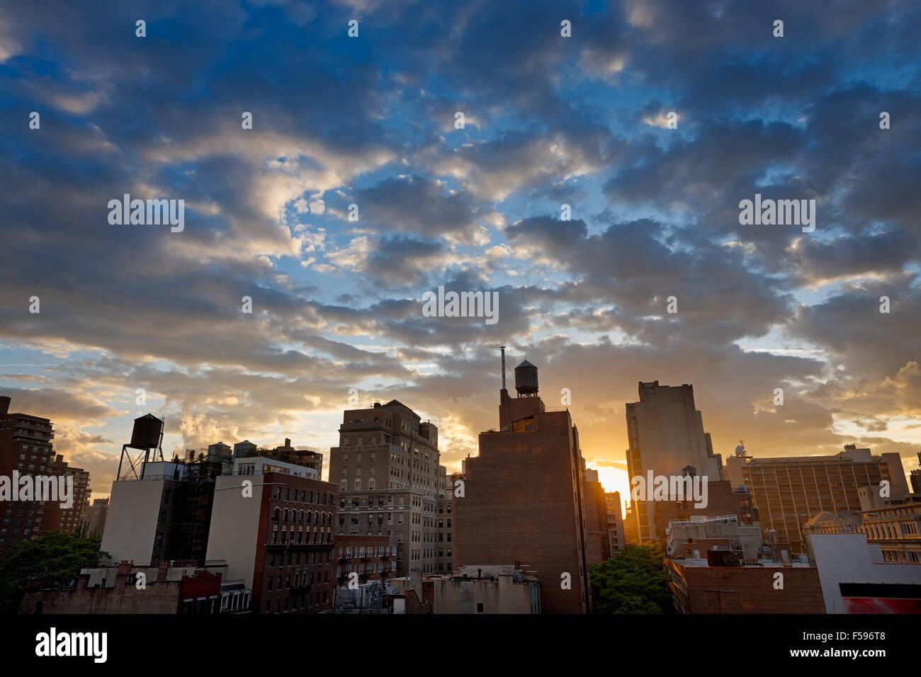 New York City, Chelsea-Viertel und die Skyline bei Sonnenuntergang mit Wassertanks punktiert. Entlang der 8th Avenue, Stockbild